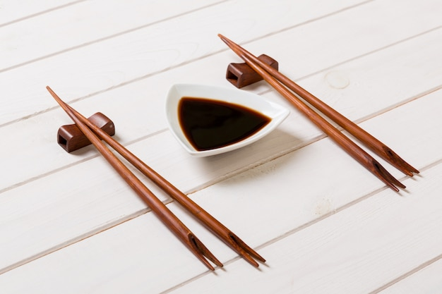 Sauce de soja avec des baguettes sur fond de table en bois blanc Photo Premium