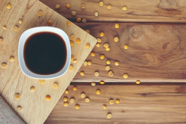 Sauce de soja qui est placé sur le bois avec des graines de soja crues dispersées autour. Photo gratuit