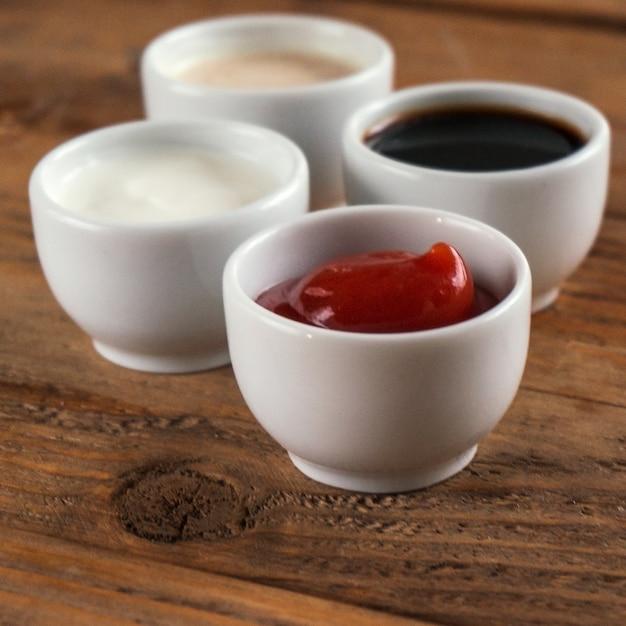 Sauces Ketchup, Moutarde, Mayonnaise, Crème Sure, Sauce Soja Dans Des Bols D'argile Sur Bois Photo Premium