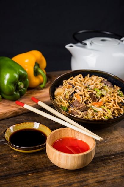 Sauces et nouilles thaïlandaises frites avec des baguettes sur une table en bois Photo gratuit