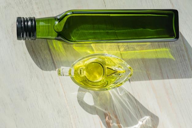 Saucière En Verre Avec De L'huile D'olive Extra Vierge Et Une Bouteille Verte Sur Une Table En Bois. Photo Premium