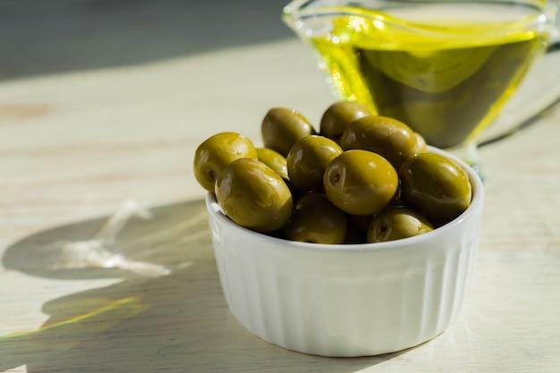 Saucière En Verre Avec De L'huile D'olive Extra Vierge Et Des Olives Vertes Fraîches Sur Une Table En Bois. Photo Premium