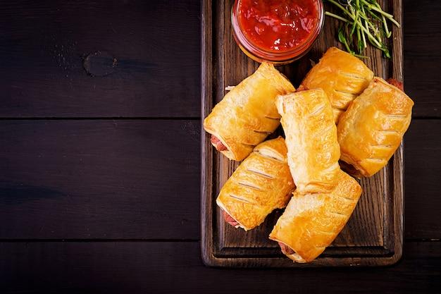 Saucisse Dans La Pâte Sur Une Planche De Bois Avec Sauce Tomate Photo Premium