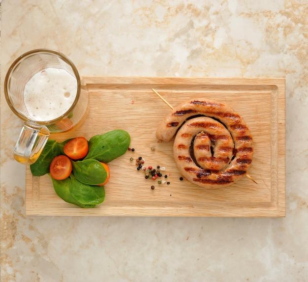 Saucisse grillée en spirale avec chope de bière, épinards et tomates Photo Premium