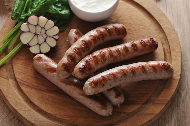 Saucisses De Bratwurst Grillées Avec Sauce, épinards Et Ail Photo Premium