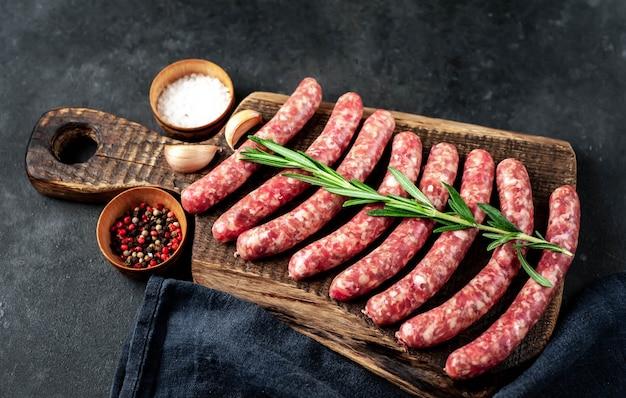 Saucisses Crues Aux épices Sur Une Planche à Découper Sur Un Fond De Pierre Photo Premium