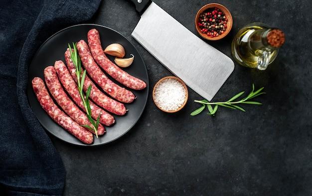 Saucisses Crues Aux épices Sur Une Plaque Noire Sur Fond De Pierre Photo Premium