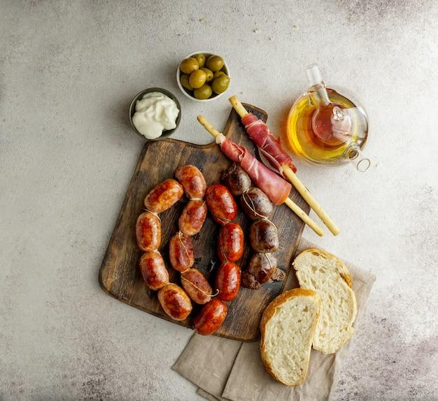 Saucisses Espagnoles Rôties Sur La Planche à Découper - Butifarra Blanca, Chorizo, Morcilla De Cebolla, Jamon Et Aïoli Sause à L'ail Photo Premium
