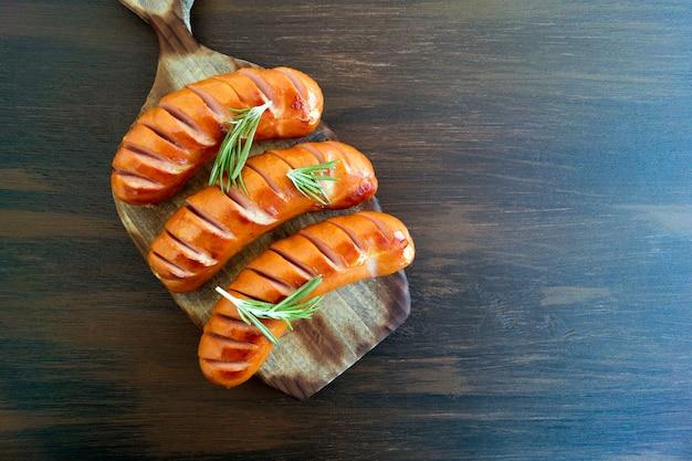 Saucisses frites sur une poêle en fonte. sur le tableau Photo Premium