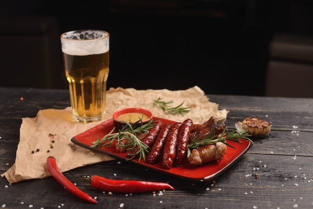 Saucisses grillées au romarin et sauce à la moutarde. dans une assiette rouge sur une table en bois Photo Premium
