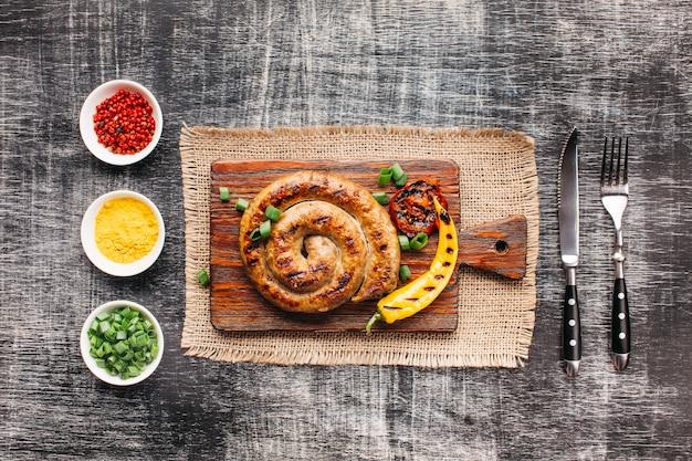 Saucisses grillées en spirale faites maison sur une planche à découper près d'ingrédients sains disposés en rangée Photo gratuit