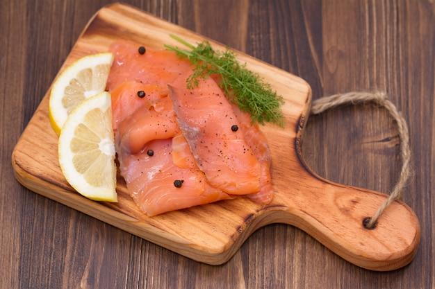 Saumon au citron et poivre noir sur planche de bois brun Photo Premium