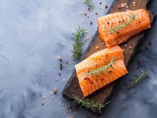 Saumon cru sur une planche de bois aux herbes Photo Premium