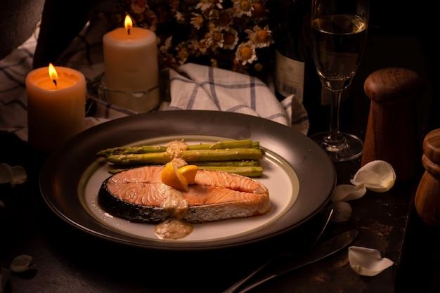 Saumon grillé et asperges sur assiette avec verre de vin blanc à l'heure du dîner Photo Premium