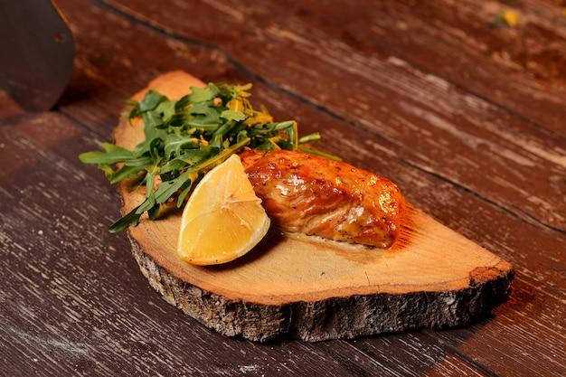 Saumon grillé au citron et à la roquette. sur une planche de bois. Photo Premium
