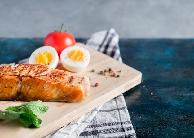 Saumon rôti avec œuf à la coque sur table bleue Photo gratuit