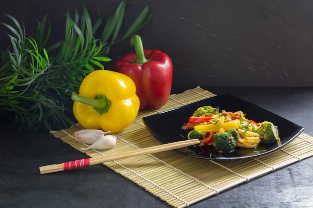 Sauté De Nouilles Japonaises Aux Légumes Sur Une Assiette Noire Avec De La Sauce Soja Et Ingrédients Sur Une Natte De Bambou Photo Premium