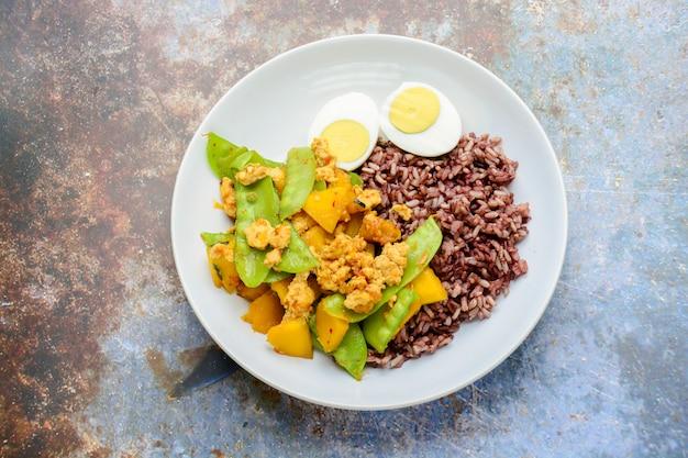 Sauté de pois mange-tout à la citrouille et au poulet, servi avec riz brun et œuf à la coque Photo Premium