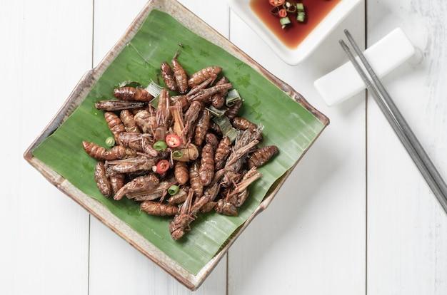 Sauterelles frites et vers à soie frits vermiformes frits, insectes mangeurs comestibles et nourriture locale à thailan Photo Premium