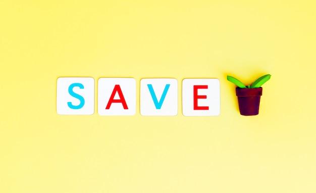 Sauvegarder l'arbre lettre avec petit arbre de la plante pour le concept de jour de l'écologie et de la terre. Photo Premium