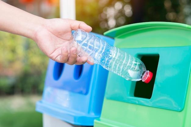Sauvez le concept du monde, jetez à la main une bouteille en plastique dans la corbeille à papier Photo Premium