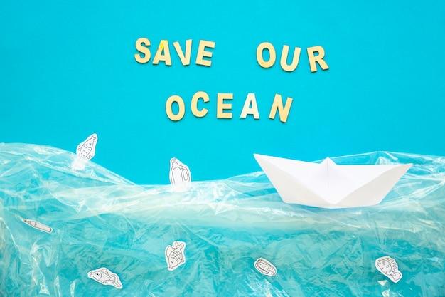 Sauvons nos mots de l'océan et bateau en papier Photo gratuit