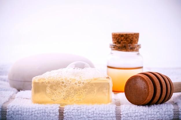 Savon de spa à base de plantes sur une serviette de bain blanche avec du miel isoler sur fond blanc. Photo Premium