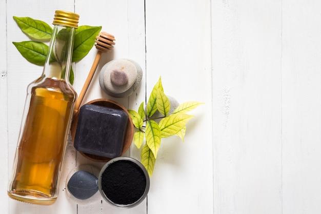 Savon spa noir à base de charbon activé et de miel sur un fond en bois blanc Photo Premium