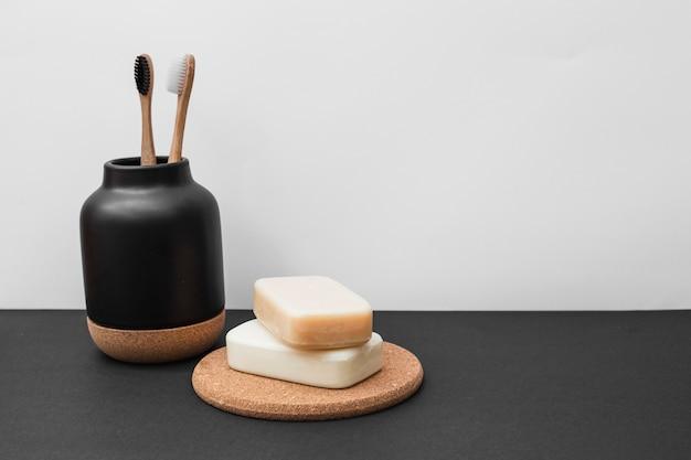 Savons et brosse à dents sur une surface noire Photo gratuit