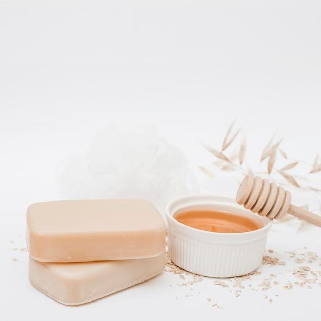 Des savons; mon chéri; louche et luffa au miel sur une surface blanche Photo gratuit