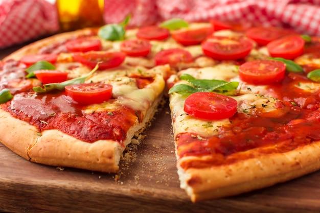 Savoureuse pizza avec une tranche coupée sur une planche à découper Photo gratuit