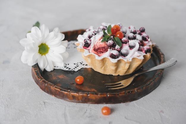 Savoureuse tarte aux fruits avec une fourchette et des fleurs sur un plateau rond en bois Photo gratuit