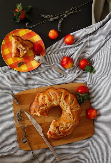Savoureuse tarte aux prunes sur le plateau en bois et prunes rouges sur la serviette décapée sur le tableau noir avec des fleurs Photo Premium