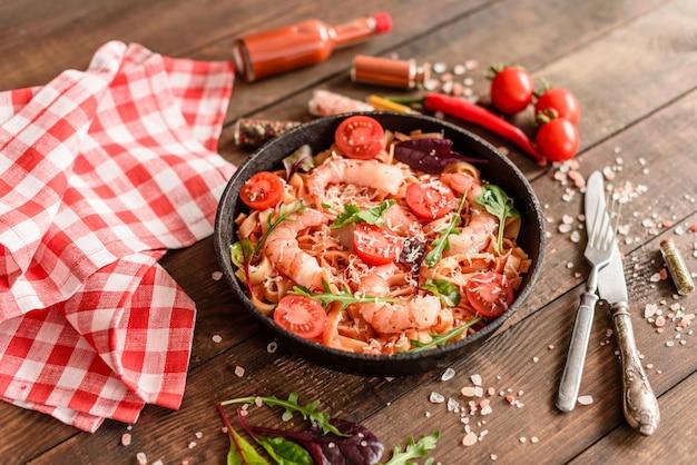 Savoureuses pâtes aux crevettes et à la tomate sur une poêle à frire Photo Premium