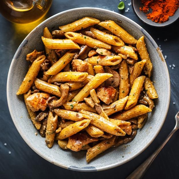 Savoureuses Pâtes Penne Aux Champignons En Sauce. Servi Sur Assiette. Carré Photo Premium
