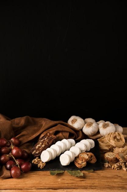Savoureux aliments crus sur une table en bois contre du papier peint foncé Photo gratuit