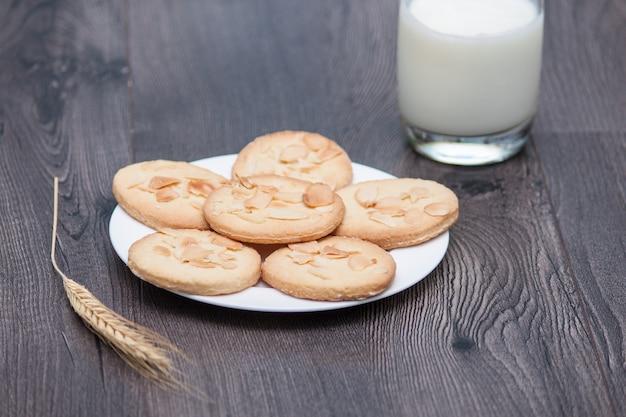 Savoureux biscuits biscuits aux amandes et au blé sur la plaque sur un fond en bois avec verre Photo Premium