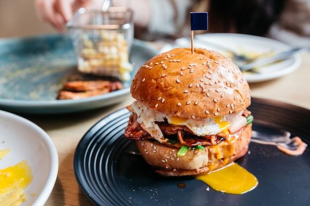 Savoureux burger avec oeuf au plat et jaune servis avec des frites dans une assiette noire sur une table en bois. Photo Premium