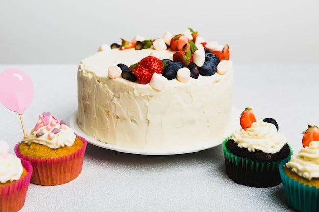 Savoureux gâteau frais aux baies et aux petits muffins Photo gratuit