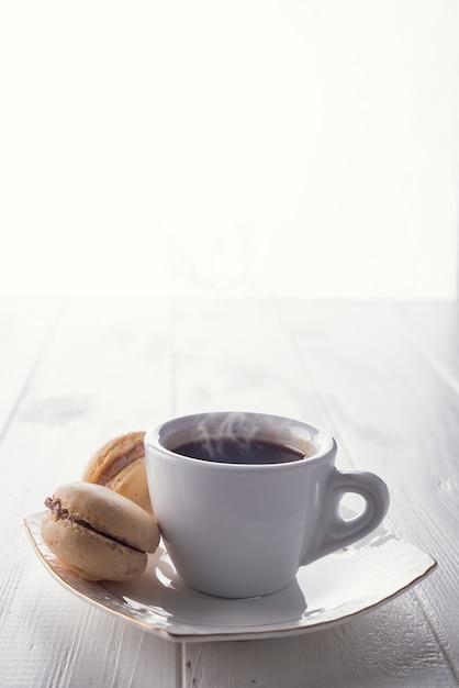 Savoureux macarons sucrés et tasse à café. macarons sur un fond en bois blanc. espace de copie Photo Premium