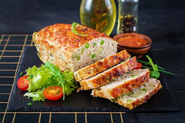 Savoureux pain de viande haché fait maison au poulet, aux pois verts et au brocoli sur un tableau noir. Photo Premium