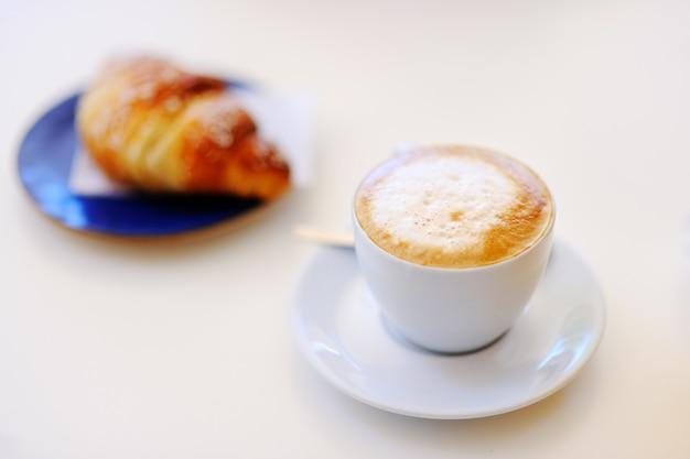 Savoureux petit déjeuner dans un café de rue italien - tasse de café et croissant sur table blanche Photo Premium