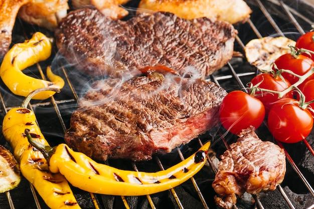 Savoureux Steaks De Bœuf Sur Le Gril Avec Piment Jaune Et Tomates Cerises Photo gratuit