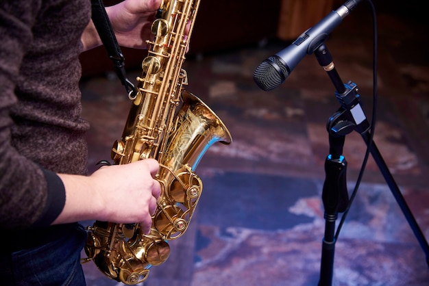 Saxophone doré entre les mains d'un musicien près du micro. Photo Premium