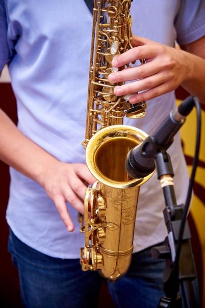 Saxophone entre les mains d'un musicien. Photo Premium