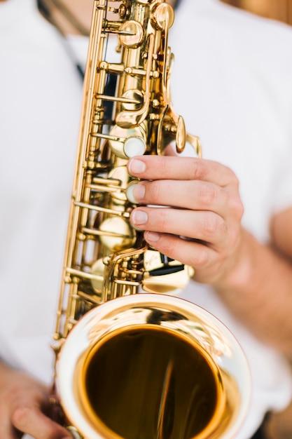 Saxophone gros plan joué par un musicien Photo gratuit