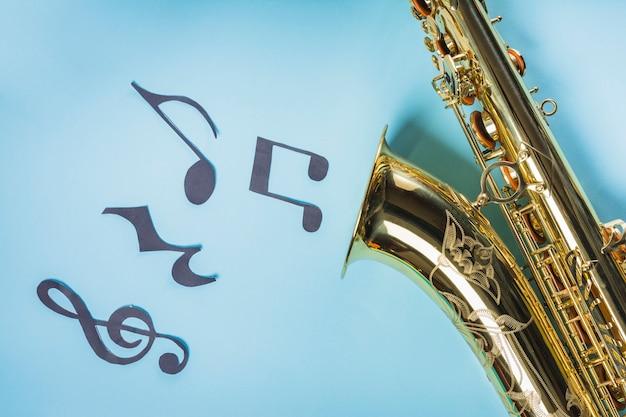 Saxophones doré avec des notes de musique sur fond bleu Photo gratuit