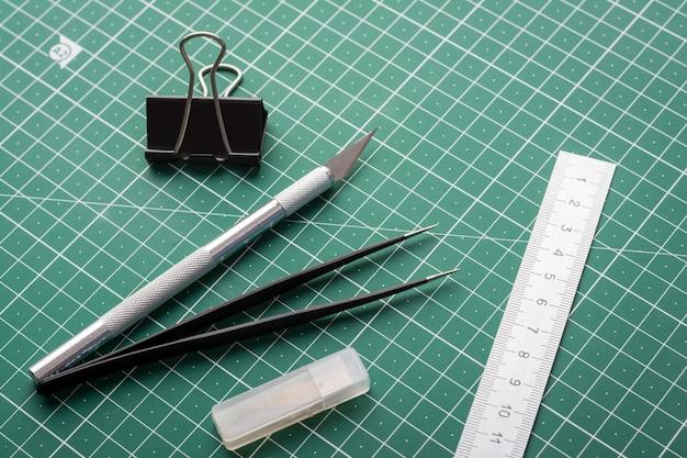 Scalpel, Pince à épiler, Règle, Trombone Et Boîte Avec Lames Pour Couteau Sur Tapis De Découpe Photo Premium