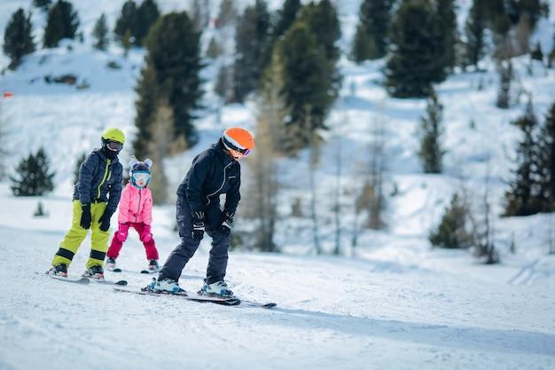 Scène d'hiver: un groupe d'enfants apprend à skier Photo Premium
