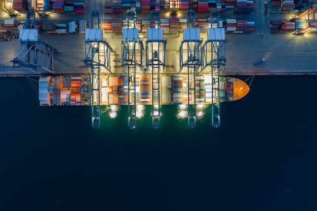 Scène de nuit vue aérienne du port de la cargaison de chargement du navire dans la logistique d'entreprise d'import-export. transport de marchandises. logistique d'entreprise d'expédition. cargo de commerce et d'expédition au port. Photo Premium